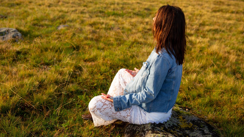Beate Wollmann sitzt meditierend auf einer Wiese